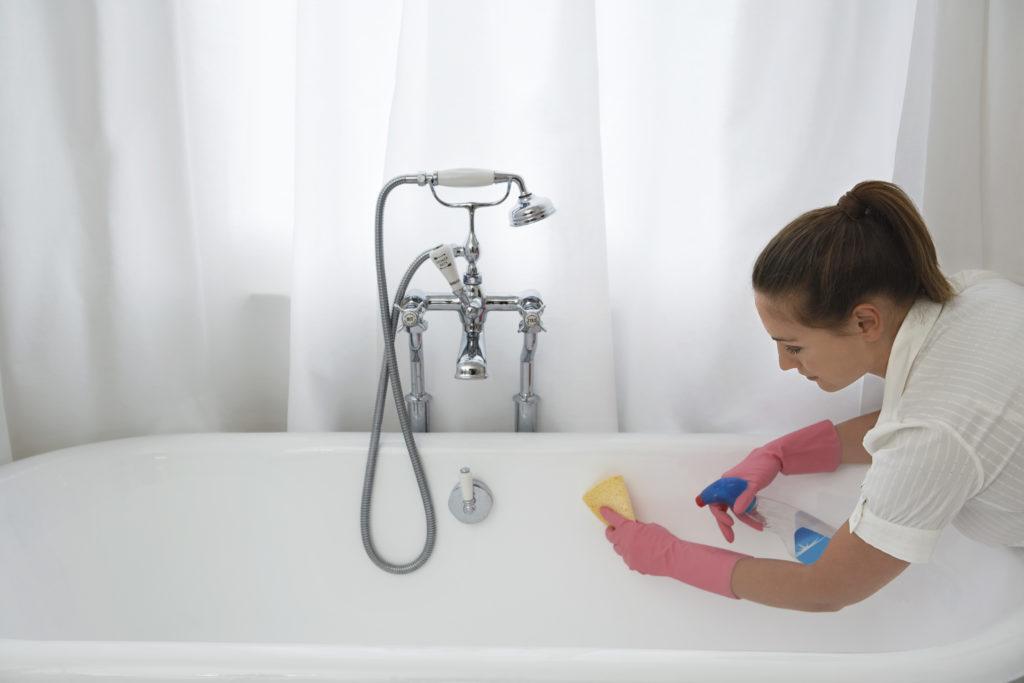 Frau die eine Badewanne reinigt